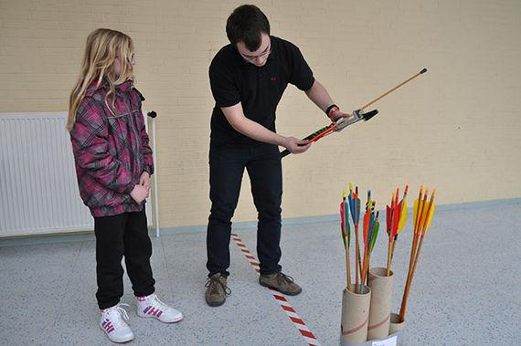 Trainer erklärt Schülerin den Umgang mit Pfeil und Bogen.